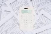 pohled shora z bílých kalkulačka s daňových formulářů na pozadí