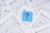 pohled shora na otazník na modrou kartu s daňových formulářů na pozadí