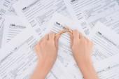 oříznutý pohled přízvučné ženy lámání tužka s daňových formulářů na pozadí