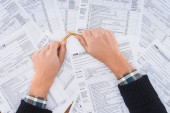 cropped view of stressed man breaking pencil with tax forms on background
