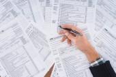 Teilansicht eines Mannes, der Stift in der Hand hält und Steuerformulare mit Kopierplatz ausfüllt