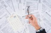 oříznutý pohled člověka drží brýle s Kalkulačka a daňové formuláře na pozadí