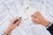 oříznutý pohled člověka vyplňování daňových formulářů a používání kalkulačky