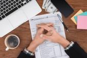 částečný pohled člověka se sepjatýma rukama, sedí u stolu s daňových formulářů a laptop