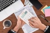 oříznutý pohled člověka pomocí kalkulačky daňové formuláře a laptop na pozadí