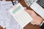Selektivní fokus člověka pomocí kalkulačky s daňových formulářů na pozadí
