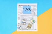 pohled shora daňového formuláře, peníze rohlíky a karta se slovo daň na modré a žluté pozadí