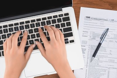 partial view of woman typing on laptop with tax form and pen on background