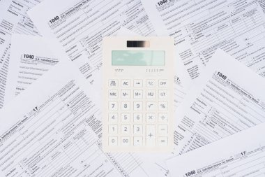 top view of white calculator with tax forms on background