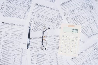 top view of calculator, pen and glasses with tax forms on background