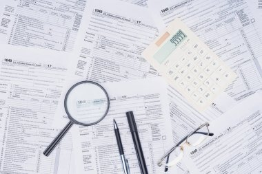 top view of calculator, magnifying glass and stationery with tax forms on background