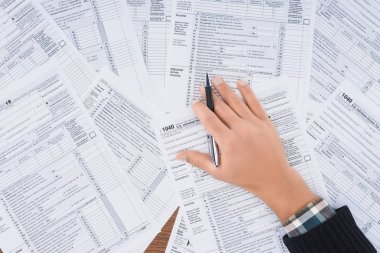 cropped view of man holding pen and filling tax forms with copy space