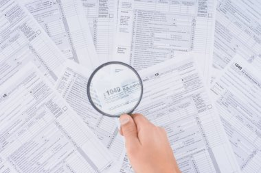 cropped view of man holding magnifying glass over tax forms