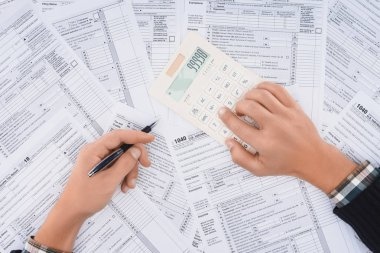 cropped view of man filling tax forms and using calculator