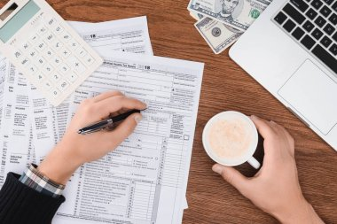 cropped view of man holding coffee cup and filling tax forms at workplace