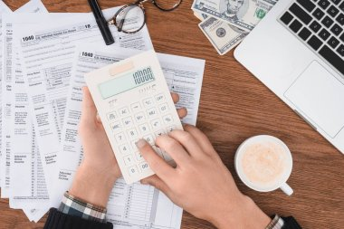 cropped view of man using calculator with tax forms and laptop on background