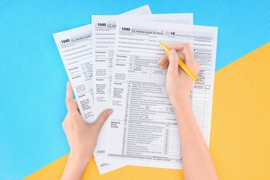 partial view of woman filling tax forms on blue and yellow background