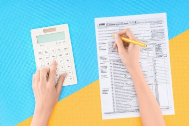 cropped view of woman using calculator and filling tax form on blue and yellow background