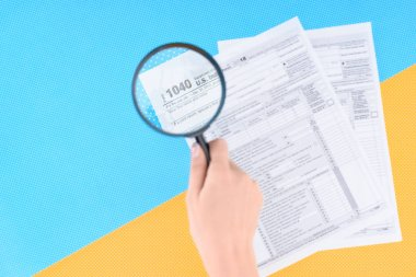 cropped view of woman holding magnifying glass over tax forms on blue and yellow background