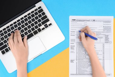 cropped view of woman typing on laptop and filling tax form on blue and yellow background