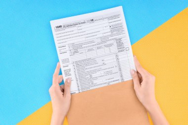 Cropped view of woman holding tax form on blue and yellow background stock vector