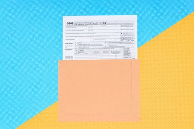 top view of tax form on blue and yellow background with copy space