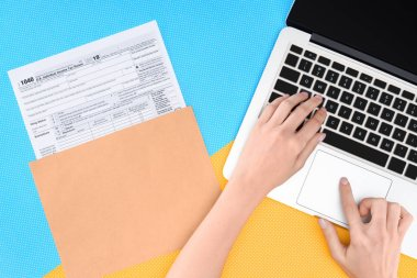 cropped view of woman typing on laptop with tax form on background