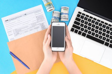 cropped view of woman holding smartphone with blank screen at workplace with laptop, tax form and money rolls on background
