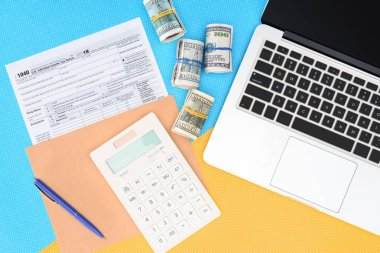 top view of tax form, money rolls and laptop on blue and yellow background