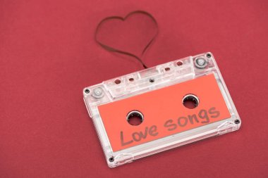 Close up view of audio cassette with lettering love songs and heart symbol made of tape isolated on red, st valentine day concept stock vector