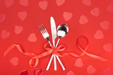 Elevated view of cutlery wrapped by festive ribbon near heart symbols isolated on red, st valentine day concept stock vector