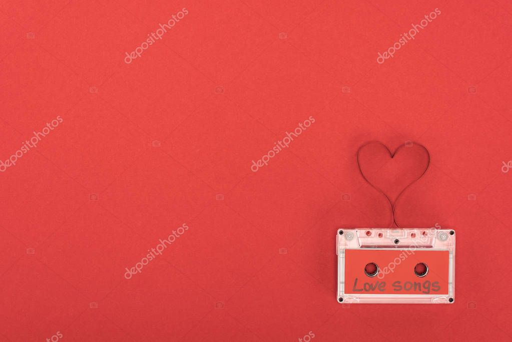 Elevated view of audio cassette with lettering love songs and heart symbol made of tape isolated on red, st valentine day concept stock vector