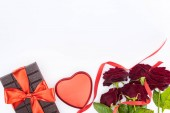 top view of chocolate wrapped by festive ribbon, red roses and heart shaped gift box isolated on white, st valentine day concept