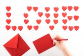 partial view of woman writing greeting card under lettering love made of red heart symbols isolated on white, st valentine day concept