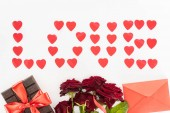 top view of lettering love made of heart symbols, chocolate wrapped by festive ribbon, red roses and envelope isolated on white, st valentine day concept