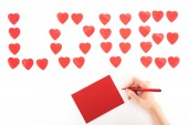 cropped image of woman writing greeting card under lettering love made of red heart symbols isolated on white, st valentine day concept