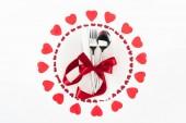 pohled shora příborů zabalené červený slavnostní stuhou uprostřed srdce symboly izolované na bílém, st valentine den konceptu