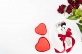 Fotografie pohled shora na talíř a příbory zabalené slavnostní stuhou, současné krabic a kytice červených růží izolované na bílém, st valentine den koncept, ve tvaru srdce
