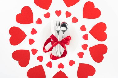 Elevated view of cutlery wrapped by red festive ribbon surrounded by heart symbols isolated on white, st valentine day concept stock vector