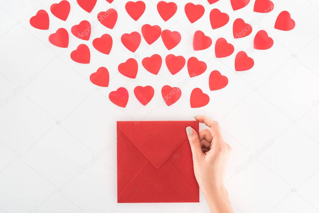Partial view of woman holding envelop under dozen red heart symbols isolated on white, st valentine day concept stock vector