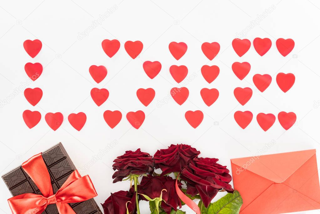 Top view of lettering love made of heart symbols, chocolate wrapped by festive ribbon, red roses and envelope isolated on white, st valentine day concept stock vector