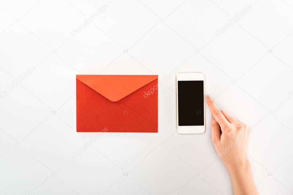 Partial view of woman holding smartphone with blank screen near red envelope isolated on white, st valentine day concept