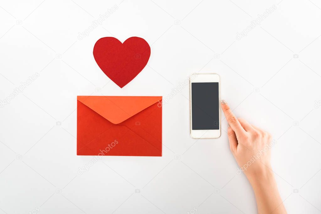 Cropped image of woman holding smartphone with blank screen near heart symbol and red envelope isolated on white, st valentine day concept