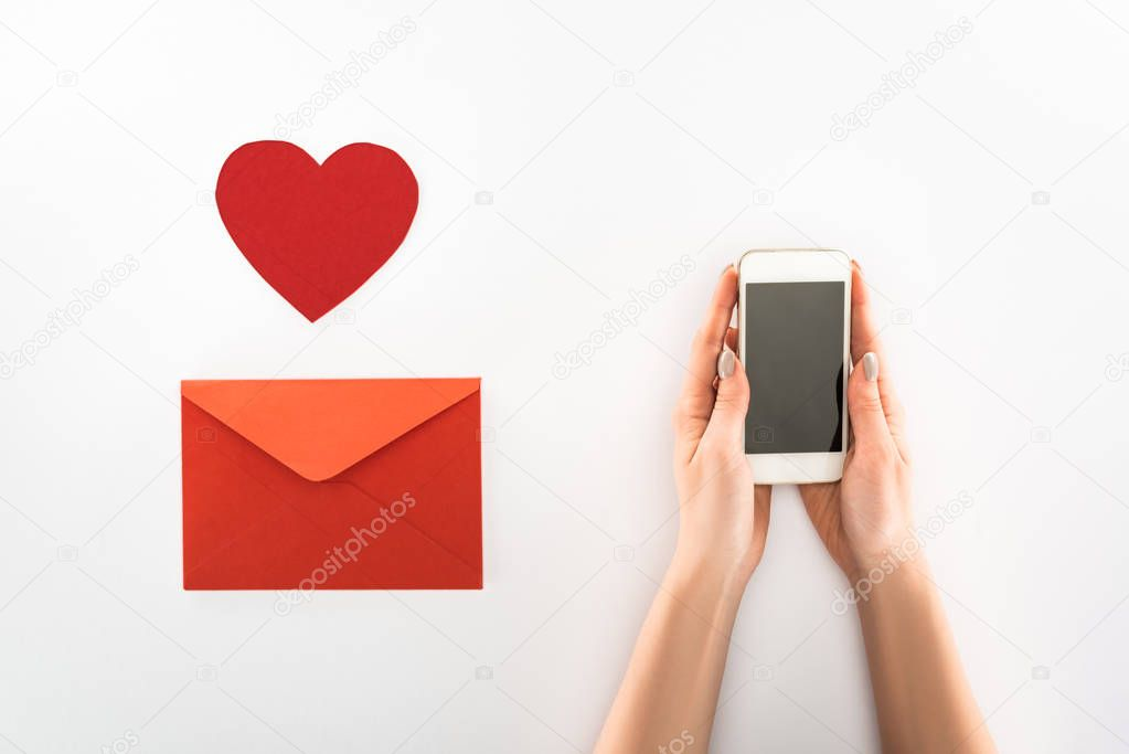 Partial view of woman holding smartphone with blank screen near heart symbol and red envelope isolated on white, st valentine day concept