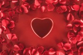 top view of beautiful heart and decorative petals on red background, valentines day concept
