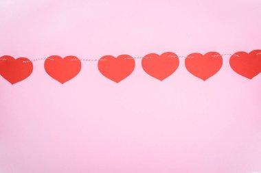 güzel dekoratif kırmızı kalpler pembe arka plan, Sevgililer günü kavramı ipte asılı