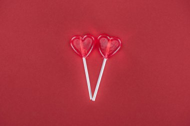 Two heart shaped lollipops on red background, valentines day concept stock vector