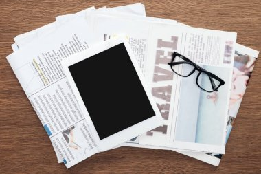 top view of tablet with blank screen, glasses and newspapers on wooden tabletop
