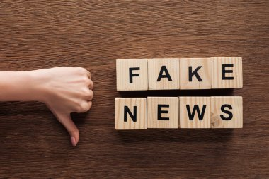 Cropped image of journalist showing thumb down to wooden cubes with words fake news at wooden table stock vector