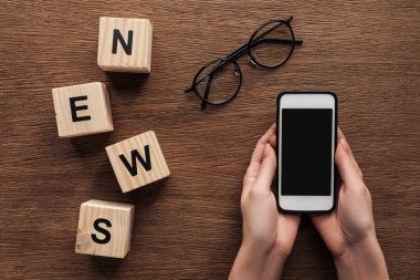 cropped image of journalist holding smartphone, wooden cubes with word news on wooden table